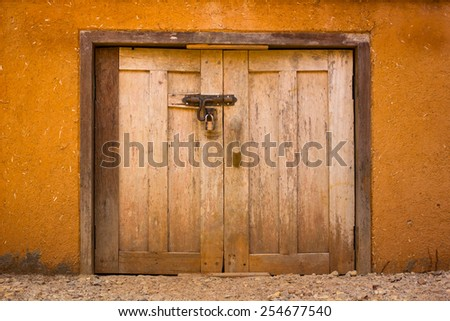 padlock and old metal hasp and wooden door - stock photo