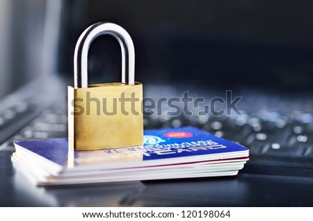 Padlock and stack of credit cards on top of laptop - stock photo