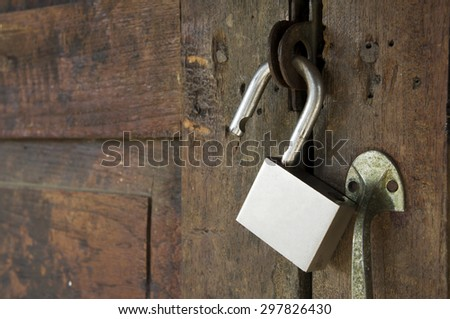 Padlock hanging on old wooden doors - stock photo