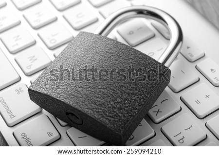 Padlock lying on white computer-keyboard closeup - stock photo