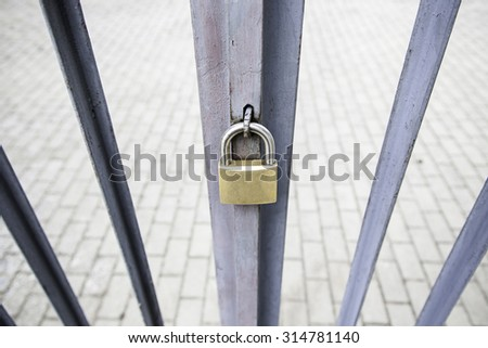 Padlock on a gate, security and protection - stock photo