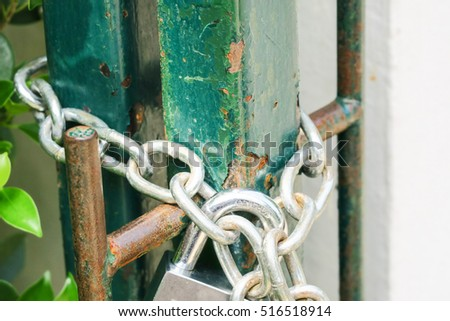 Padlock on a steel chain link fence. Rustic steel fence and safety padlock