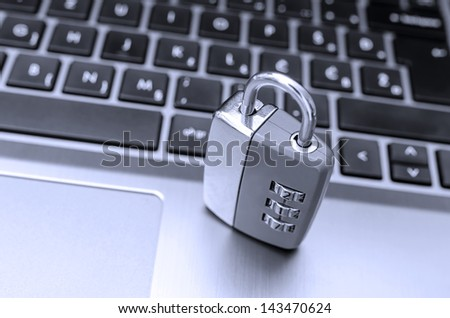 Padlock on laptop keyboard. Concept of protection against internet piracy. - stock photo