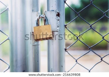 Padlock on metal cage door (security business concept) - stock photo
