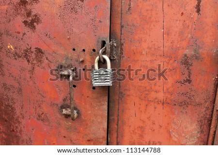 padlock on the rusty door - stock photo