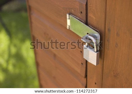 Padlock on wooden shed door