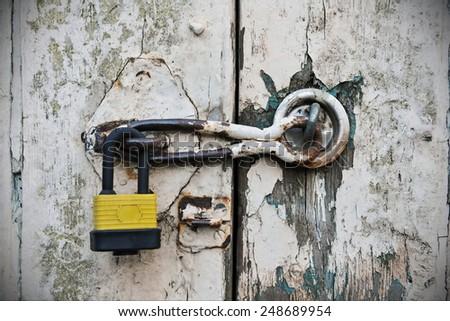 Padlock Securing an Old Weathered Door - stock photo