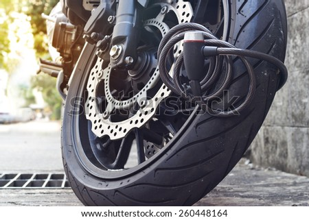 padlock security lock blocking the motorcycle wheel on street, anti-theft system - stock photo