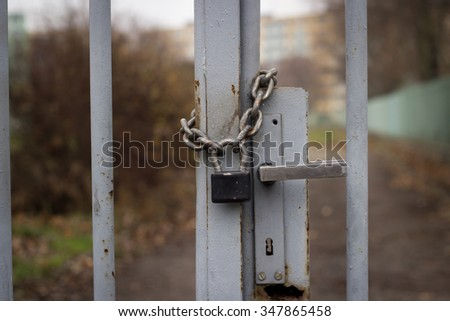 Padlock with iron chain on the old gray fence; locked location - stock photo