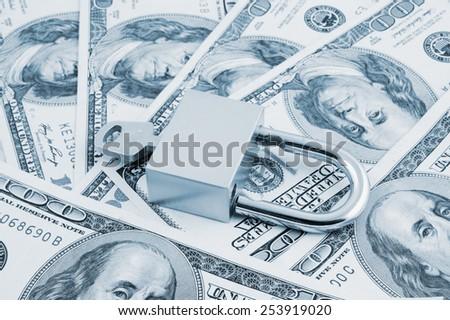 Padlock with key on dollars background - stock photo