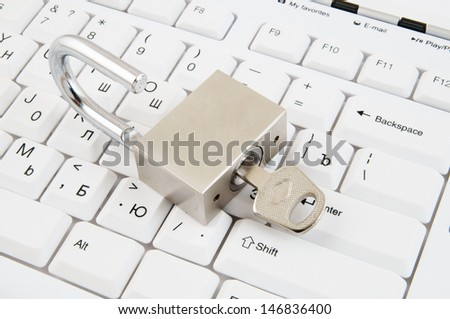 Padlock with key on white computer keyboard