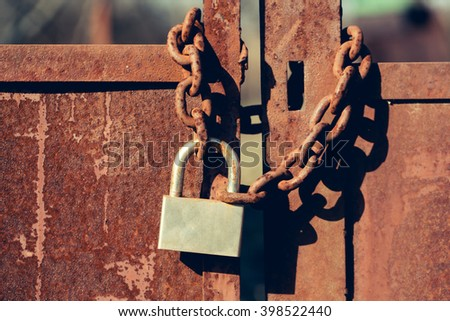 Padlock with shackle and locking mechanism closeup one portable lock on chain on unpainted rusty metal gate doors outdoor on blurred background - stock photo