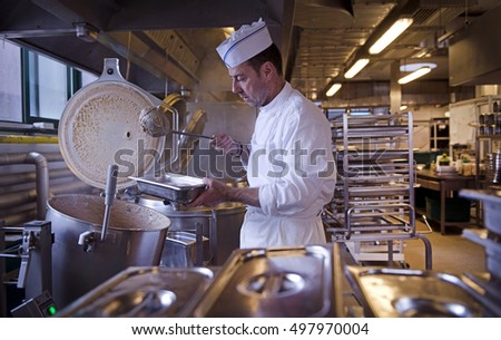 PADOVA ITALY-MAY 14, 2015: cook at work on a canteen industrial kitchen, in Padova.