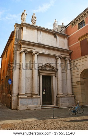 PADUA, ITALY - FEBRUARY 24, 2012:  The tiny chapel with scenic marble facade is tilted on the house wall and the bicycle parked next to its door, on February 24 in Padua.
