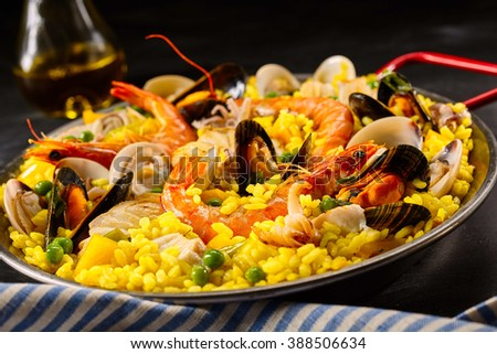 Paella a la margarita with shellfish including pink prawns, clams and mussels on saffron rice with peas for a delicious seafood meal, close up view