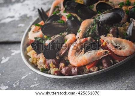 Paella in the metal plate on the metal background horizontal