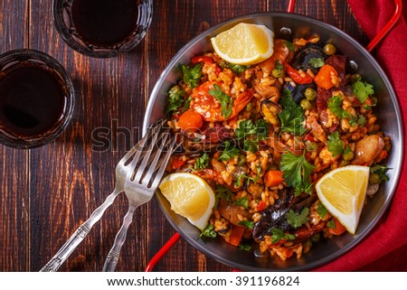 Paella with chicken, chorizo, seafood, vegetables and saffron served in the traditional pan, top view. - stock photo