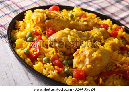 Paella with chicken drumsticks and vegetables close-up on a plate. horizontal