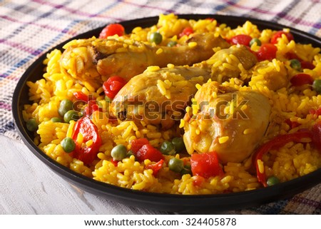 Paella with chicken meat and vegetables close up on a plate. horizontal