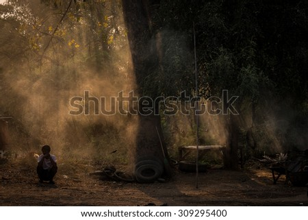 PAGAN, MYANMAR- MARCH 10, 2015: The man sitting under the tree in Pagan, Myanmar - stock photo