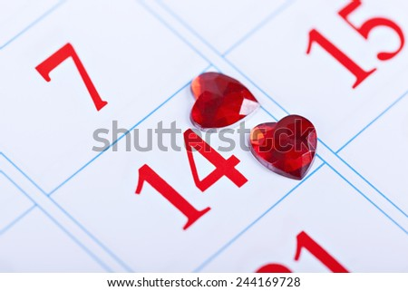 page calendar with two red hearts on the date of February 14 Valentine's Day - stock photo