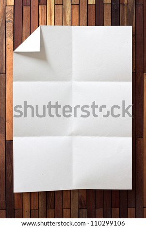 page of White paper folded and wrinkled on wood background with shadow