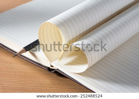 Pages of a book curved into a heart shape. Valentines day - stock photo