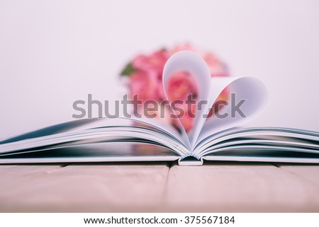 Pages of a book curved into a heart shape. vintage tone - stock photo