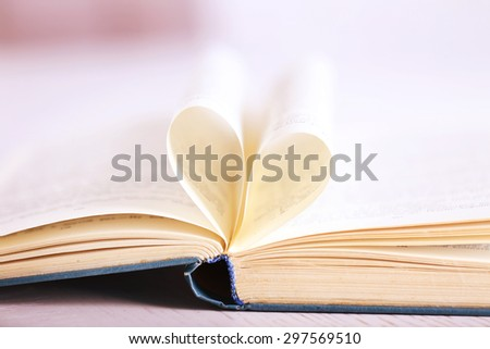 Pages of book curved into heart shape, close up