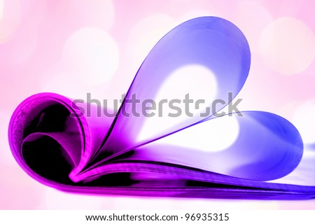 Pages of magazine curved into a heart shape with lights in the background - stock photo