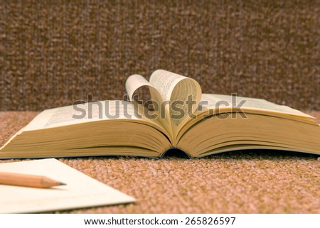 Pages of open book rolled in heart shape on table.