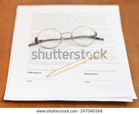 pages of sales contract, golden pen and eyeglasses on wooden table