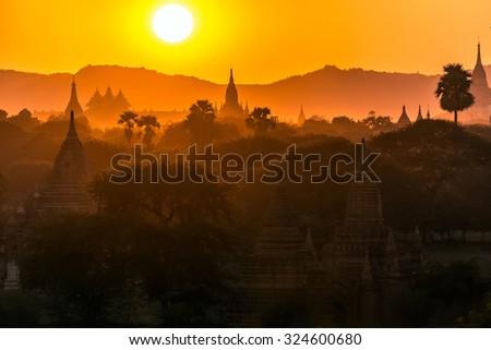 Pagoda landscape under a warm sunset in the plain of Bagan, Myanmar (Burma) - stock photo