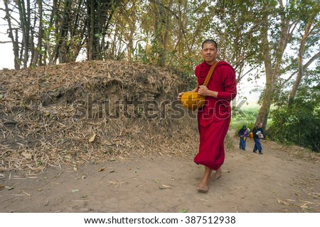 Pai, Thailand February 21, 2016: A Theravada Buddhist walks on a forest path with followers in the woods after receiving morning alms near Pai, Thailand on February 21, 2016.