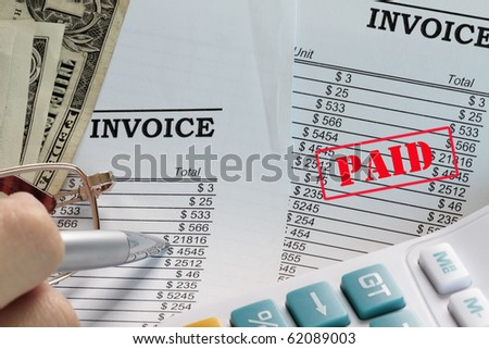 Paid invoice in a spreadsheet with dollars and pen. - stock photo