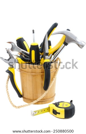 pail with tool and tape measure on white background