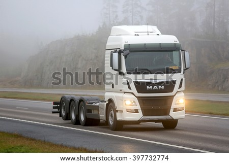 PAIMIO, FINLAND - NOVEMBER 13, 2015: New MAN TGX 35.360 D38 Truck bobtails on motorway through fog. The new MAN TGX D38 is suited for heavy-duty long-haul transport. - stock photo