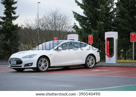 PAIMIO, FINLAND - NOVEMBER 15, 2015: White Tesla Model S electric car being charged at the Paimio Tesla Supercharger station. The Supercharger gives the Model S 270 km of range in about 30 minutes. - stock photo