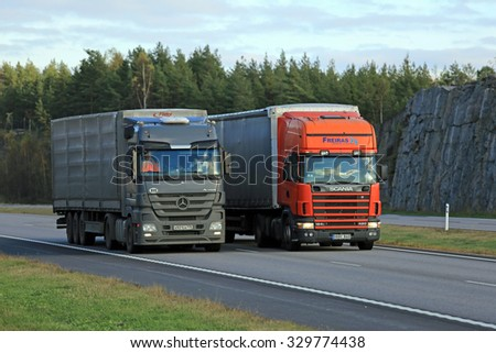 PAIMIO, FINLAND - OCTOBER 16, 2015: Scania 124L Semi overtakes another truck on motorway. Trucks with heavy cargo can be much slower uphill.  - stock photo