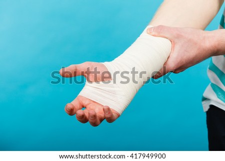Pain and injury concept. Young man holds bandaged hand. Injured part of body. Medicine and healthcare. - stock photo