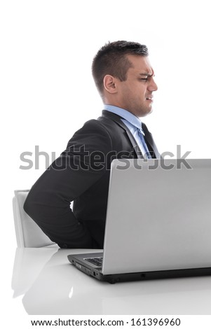 Pain: businessman sitting with backache at desk isolated on white background - stock photo