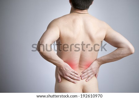 Pain in a back of the man on gray background. Red dot - stock photo
