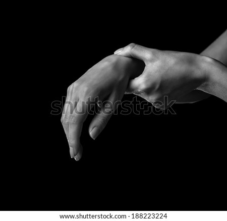 Pain in a female wrist. Woman holds her hand, monochrome image