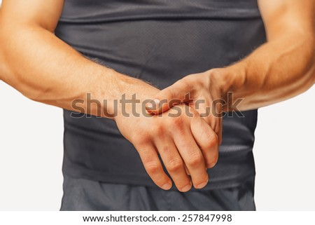 Pain in a male wrist. Man holds his hand. - stock photo