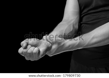 Pain in a male wrist. Man holds his hand, monochrome image - stock photo