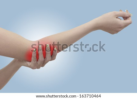 Pain in a woman elbow. Female holding hand to spot of elbow pain. - stock photo