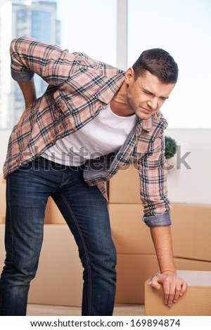 Pain in back. Young man holding hand on his back and expressing negativity while leaning at the cardboard box - stock photo