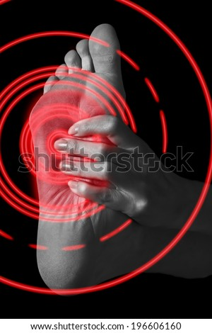Pain in the female foot, monochrome image, pain area of red color - stock photo