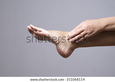Pain in the foot. Massage of female feet on a gray background - stock photo