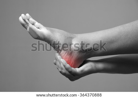 Pain in the foot. Massage of female feet. Pain in the human body on a gray background. Black and white photo with red dot - stock photo